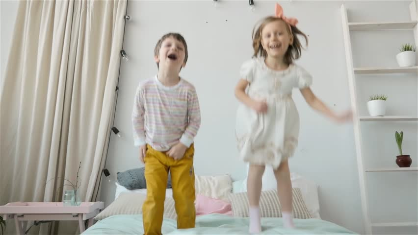 Portrait of children jumping on a bed, little boy and girl brother and sister have fun and laughing, happy kids on quarantine, coronavirus home isolation #26028536