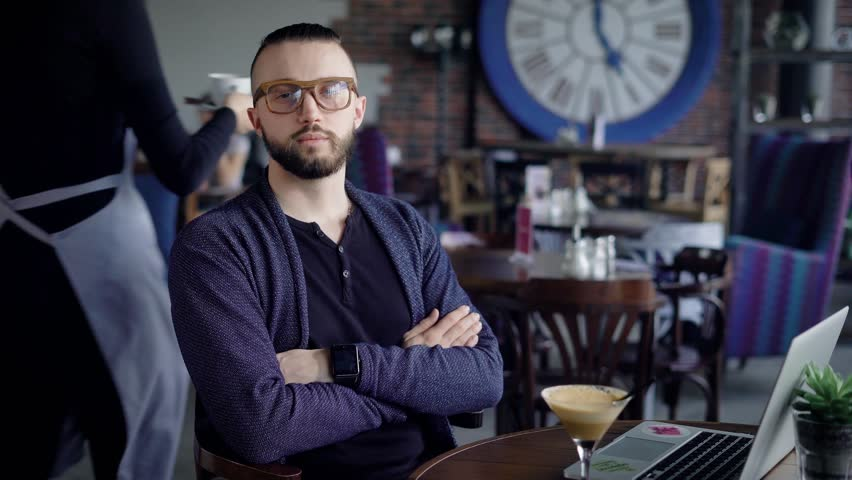 Portrait of an attractive young man in glasses. Hipster in casual clothes looks into the camera with a slight smile. Actually looks guy | Shutterstock HD Video #26030810