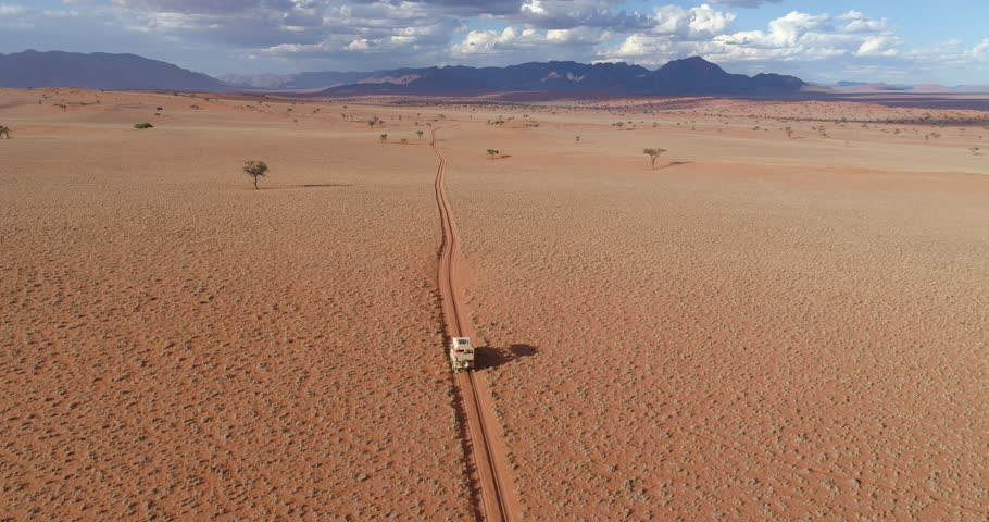 4K aerial view of safari vehicle driving on sand track road in the Namib desert