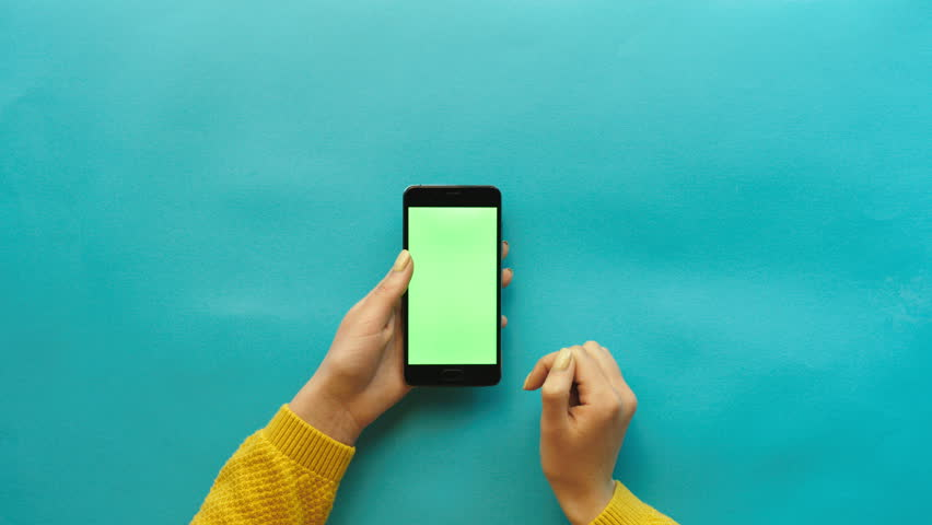 Woman using smart phone with green screen on blue table background. Female hands scrolling pages, tapping on touch screen. top view. Chroma key. Creative background | Shutterstock HD Video #26050427