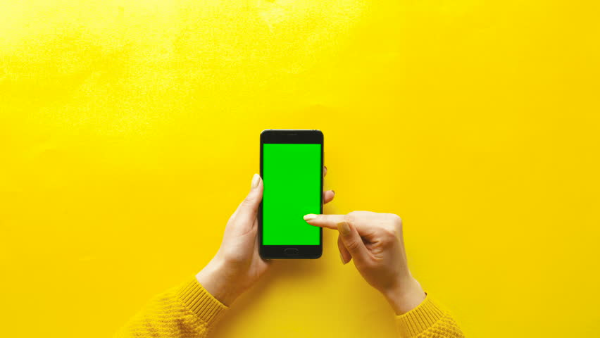 Woman using smart phone with green screen on yellow table background. Female hands scrolling pages, tapping on touch screen. top view. Chroma key. Creative background