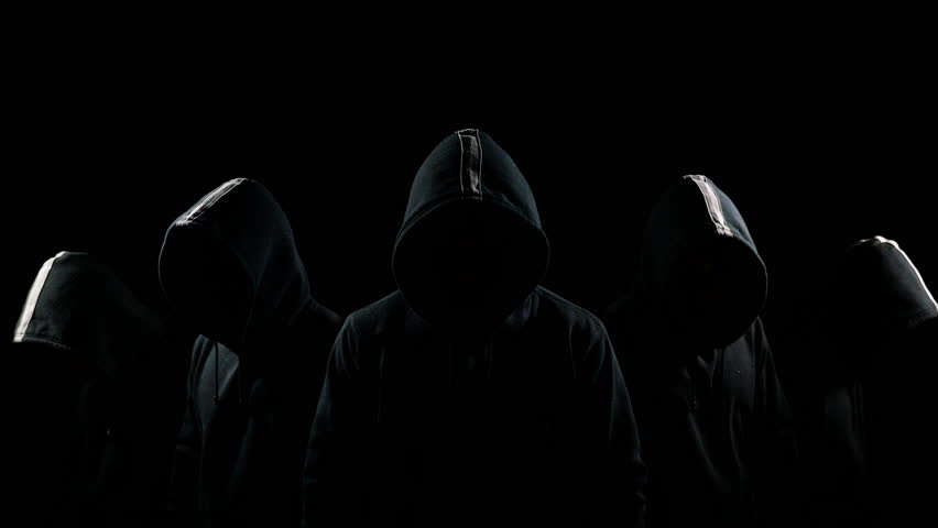 Five mysterious hooded men standing in the dark hoodies and hidden faces