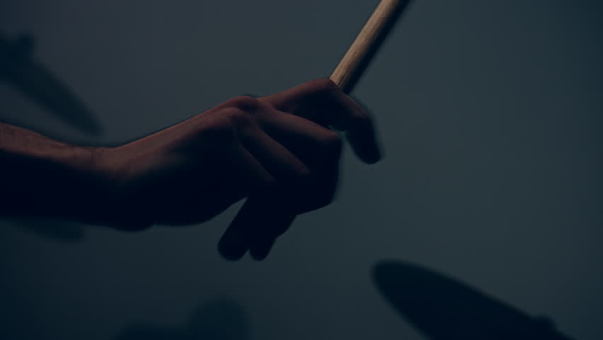Drummer plays drums kit. Drummer hand silhouette with drumstick. Close up of drummer hand playing drum plate on rock concert. Rock band performing on stage. Close up of drum plate | Shutterstock HD Video #26062424