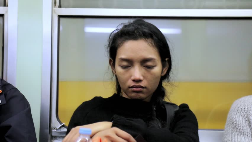 A sleepy girl is on the train. A young woman is asleep in a subway. Tired traveler sitting on a metro train.