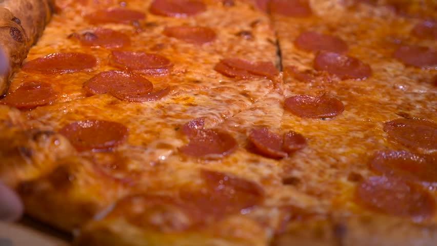 Slow Motion taking slice of pizza. Close up of a delicious slice of home baked pepperoni cheese pizza #26066963