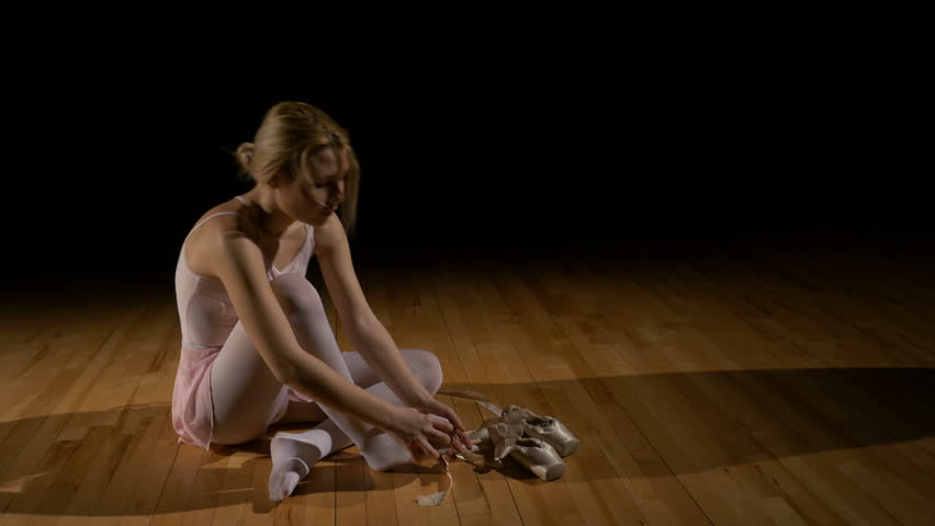 Blonde ballerina untying shoes and sitting on the floor tired