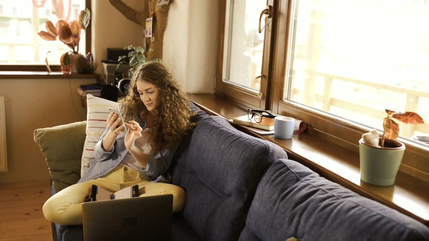 Beautiful teenage girl with smartphone sitting on couch, texting, laptop next to her. | Shutterstock HD Video #26074667