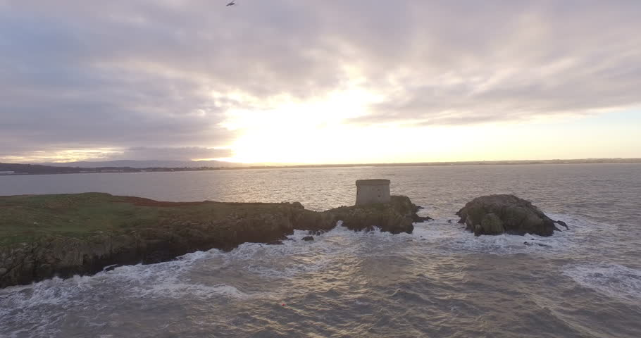Drone shot along rough coastline Ireland's eye, Ireland with a castle in forground. Shot during sunset. | Shutterstock HD Video #26081630
