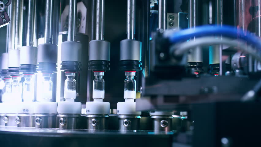 Pharmaceutical machine. Automated quality control equipment. Medical vials on production line at pharmaceutical factory. Pharmaceutical technology. Quality control at pharmaceutical industry