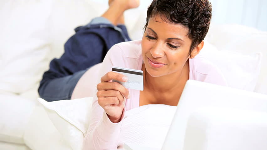 Young African American female lying home couch using credit card buy shopping online Royalty-Free Stock Footage #2608613