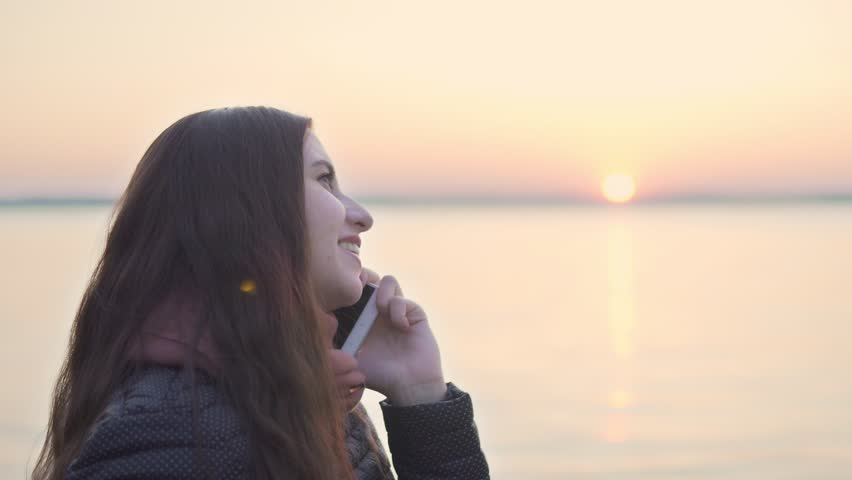 Young attractive woman talking on mobile phone on sunset background on lake. 4k   Shutterstock HD Video #26087201