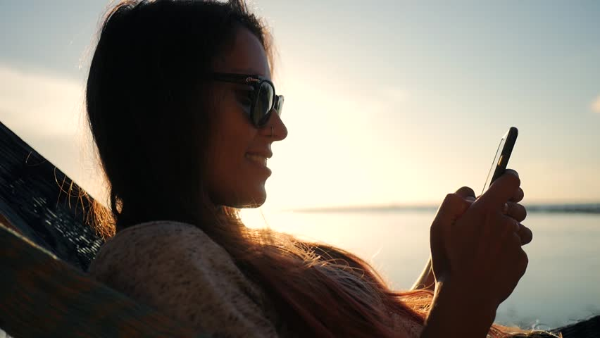 Young Smiling Mixed Race Tourist Girl in Sunglasses Using Mobile Phone in Hammock at the Beach near the Sea with Beautiful Sunset on Background. Koh Phangan, Thailand. HD Slowmotion. #26088968