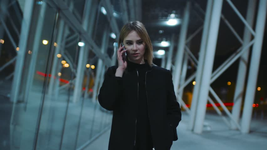 Charming young woman in a good mood in the dark clothes is near the business center in the evening. The girl is talking with someone on her smartphone. Evening in the city, good mood. | Shutterstock HD Video #26112950