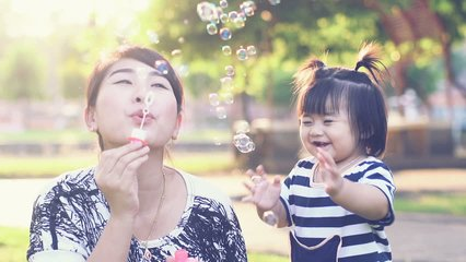 Asian Mother entertaining her baby girl by making iridescent soap bubbles