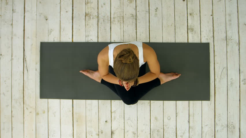 Sporty beautiful young woman practicing yoga, sitting in cross legged position