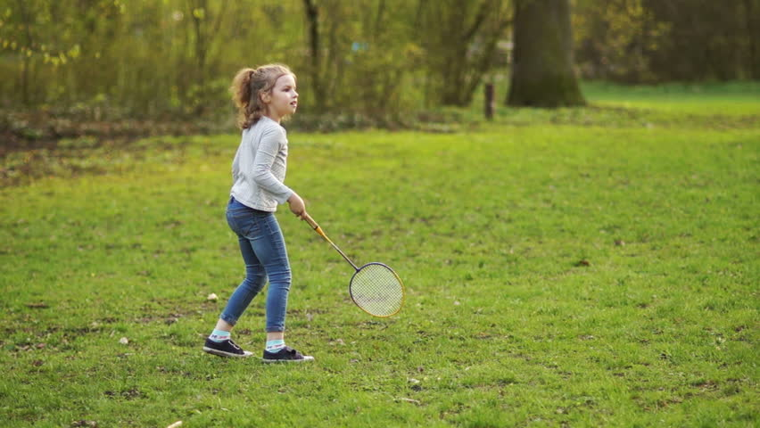 Girl playing badminton in the Park. She deftly bats the shuttlecock, then drops it and the game continues. HD
