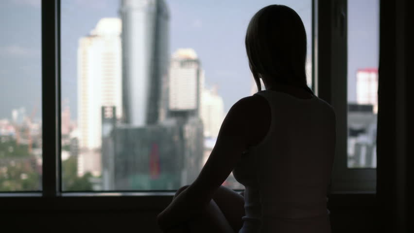 Silhouette of young woman sitting on bed and looking out of window. City skyscrapers landscape outside | Shutterstock HD Video #26151488