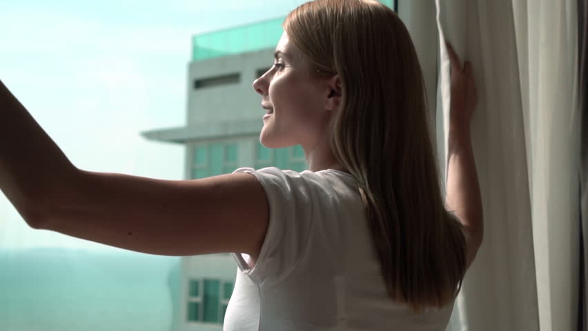 Silhouette of young woman unveiling curtains and looking out of window. Enjoying the sea view outside. Slow motion 100 fps.