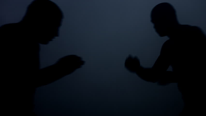 Silhouettes kick boxers fight in dark. Closeup of mma fighter silhouettes. Boxing fight in dark. Two kickboxers training at dark ring. Sparring partners fight training. Fights of mixed martial arts