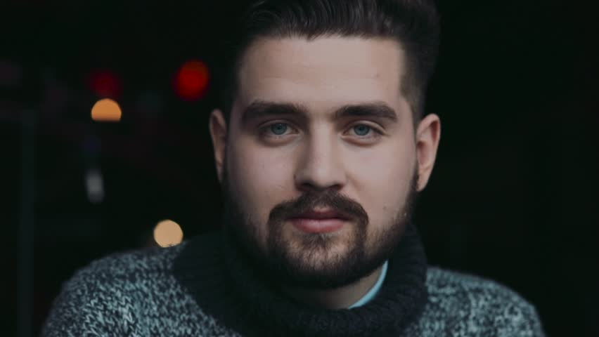 Young attractive blue-eyed bearded man in a warm sweater drinks beer, is surprised with the taste, looks right towards the camera. Bar interior on the background. Man's club, male traditions. #26157203