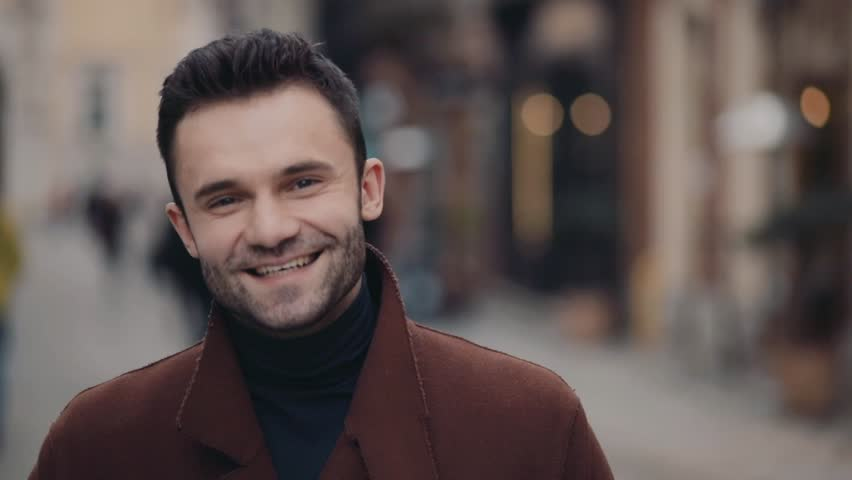 Handsome young man in casual brown coat standing in the city center and smiling brightly towards the camera. Having fun, modern man. No people around, city lights on the background. | Shutterstock HD Video #26157242