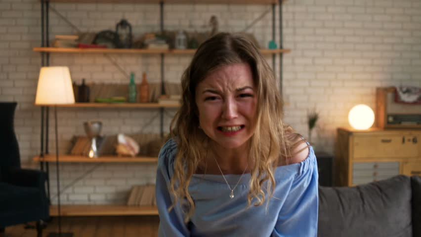 Portrait of beautiful blonde angry woman being very unhappy hysterize and shout with tears looking at the camera because of big trouble and stress