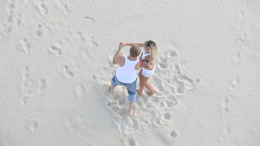Joyful attractive couple dancing with love on the summer sand