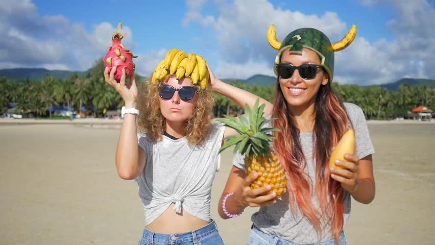 Two Carefree Young Girls Fooling on the Beach and Dancing with Exotic Thai Fruits. Vegan Dance. Phangan, Thailand. HD Slowmotion.