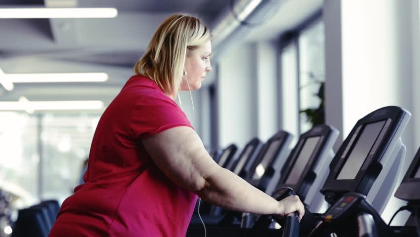 Overweight woman walking on treadmill in modern gym.