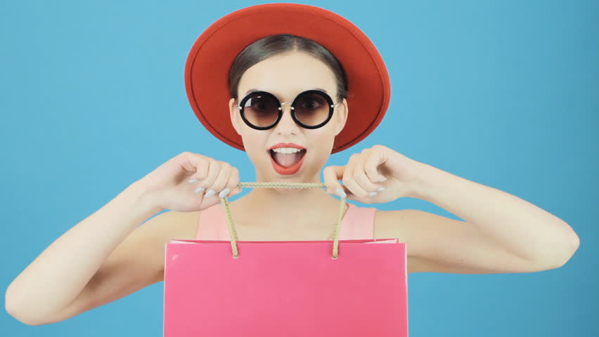 Closeup Portrait of Brunette Woman in Red Hat and Cool Sunglasses Holding Pink Shopping Bag on Blue Background in Studio. Seasonal Sale Concept.