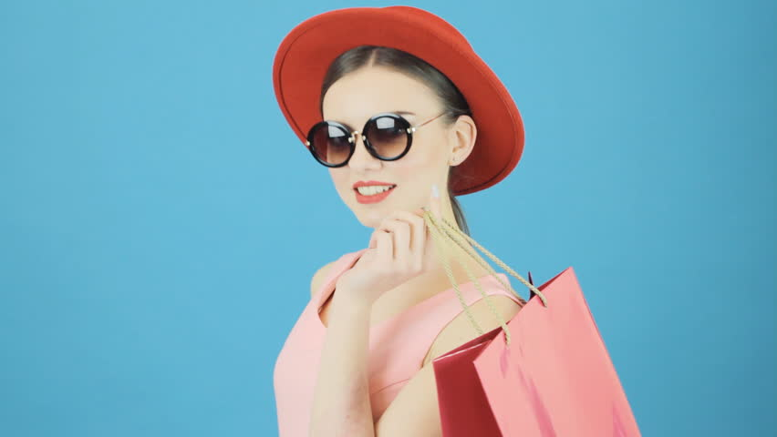 Cute Brunette in Red Hat and Sunglasses Holding Pink Shopping Bag on Blue Background in Studio. Seasonal Sale Concept. #26165603