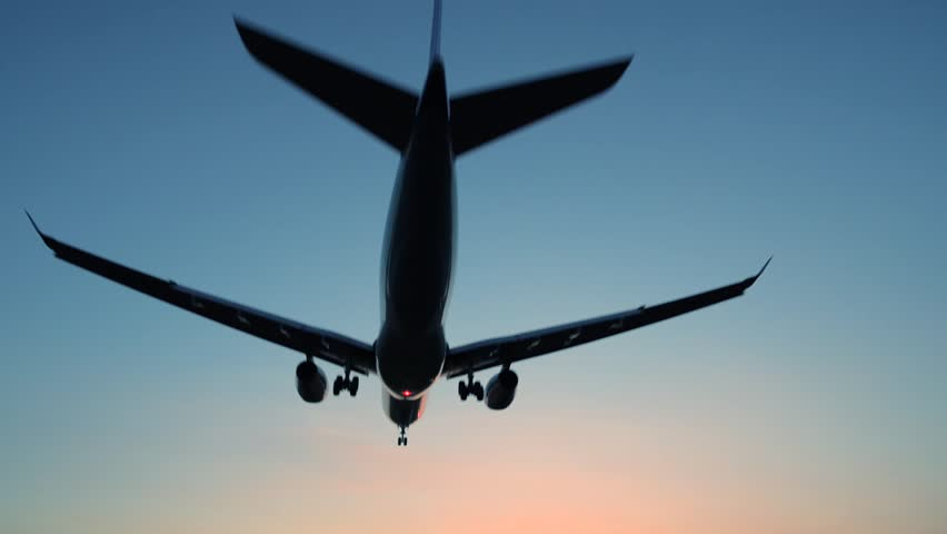 Plane flying over head, landing at airport at sunset or sunrise