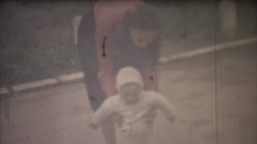 Family chronicle: Mother teach their child to walk. 8mm retro camera.