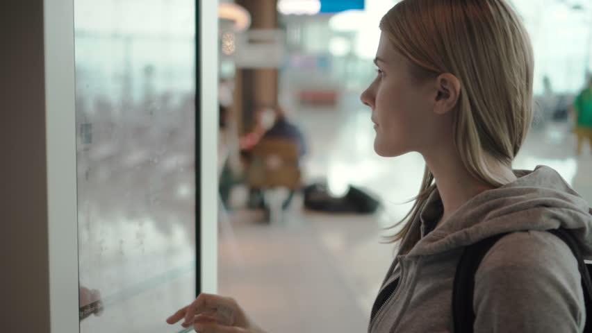 Beautiful attractive woman in airport terminal. Choosing food via self-service machine at fast food restaurant or diner