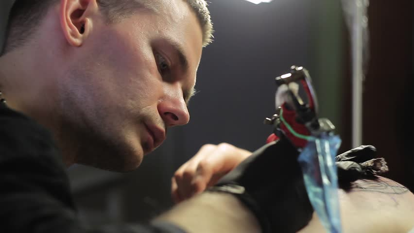 Man tattoo artist makes a tattoo on shoulder in black ink, Close-up shooting #26199521