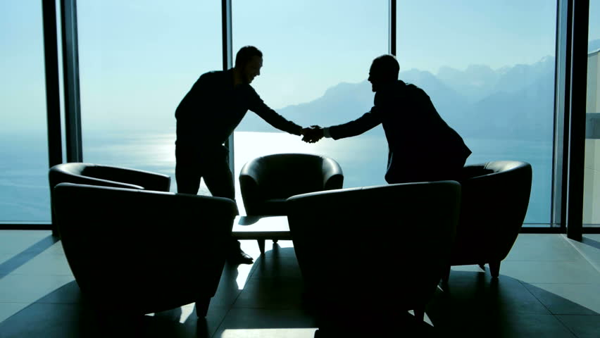lobbyist handshaking with partner after business deal agreement. businessman meeting in modern lobby talking together. two people having a conversation about financial strategy  #26200184