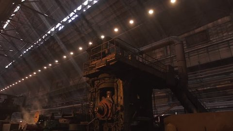 Interior of metal factory steam slow motion camera motion down long shot