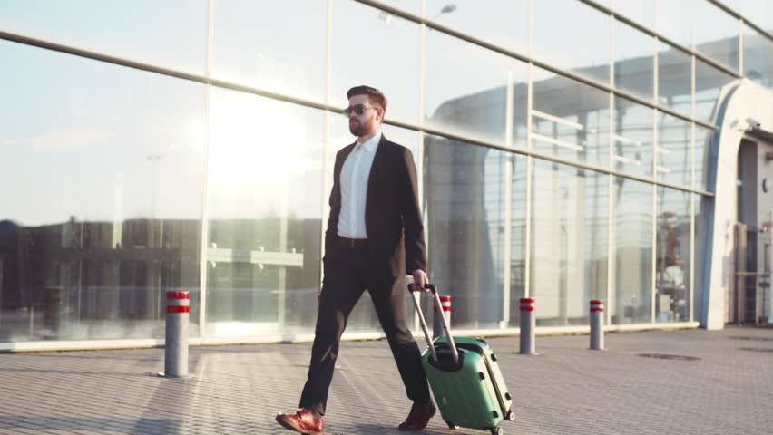 Stylish young bearded man in sunglasses exiting the airport terminal with luggage, answers the phone. Business style, traveler, modern lifestyle. Active lifestyle. | Shutterstock HD Video #26209067