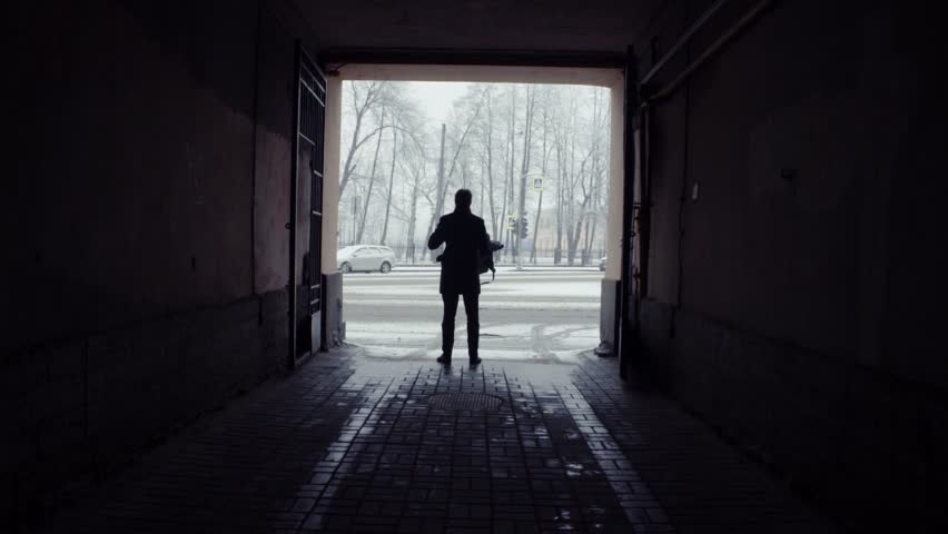 Silhouette of man with a cup of coffee standing and opening umbrella before getting out under a snowfall. Roadway on the background. Slow motion.   Shutterstock HD Video #26214365