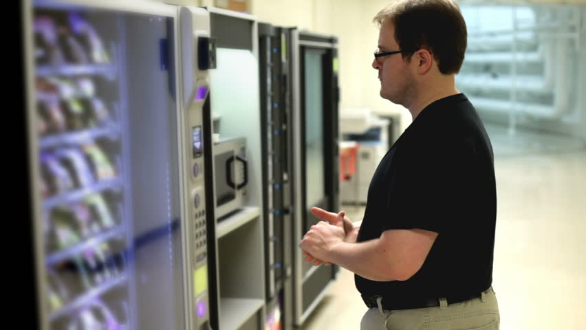 Man pondering decision at vending machine