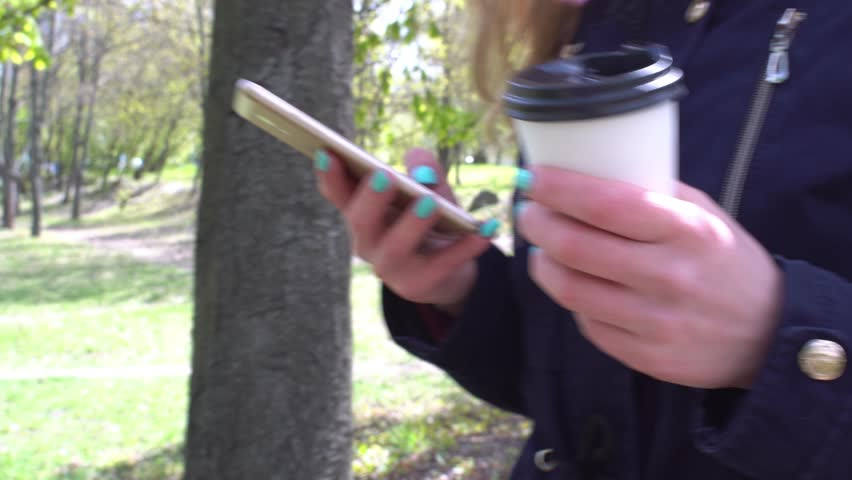 Talking on the phone, A girl is walking in the morning in a park with a smartphone and coffee steady camera shot  | Shutterstock HD Video #26232932