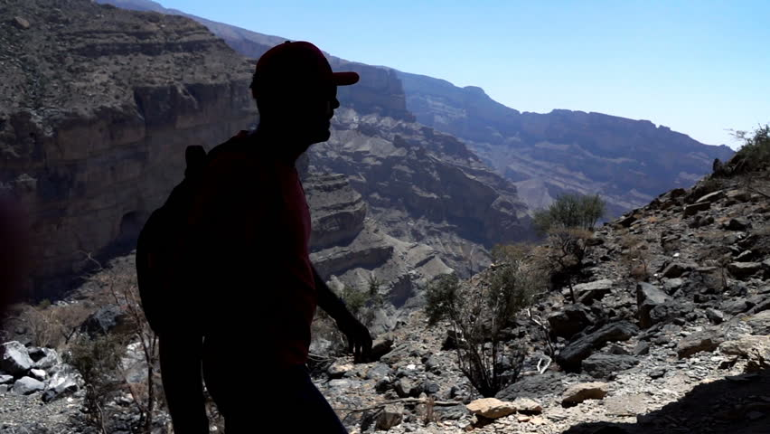 Silhouette of man trekking in the mountains near canyon, super slow motion 240fps  | Shutterstock HD Video #26248247