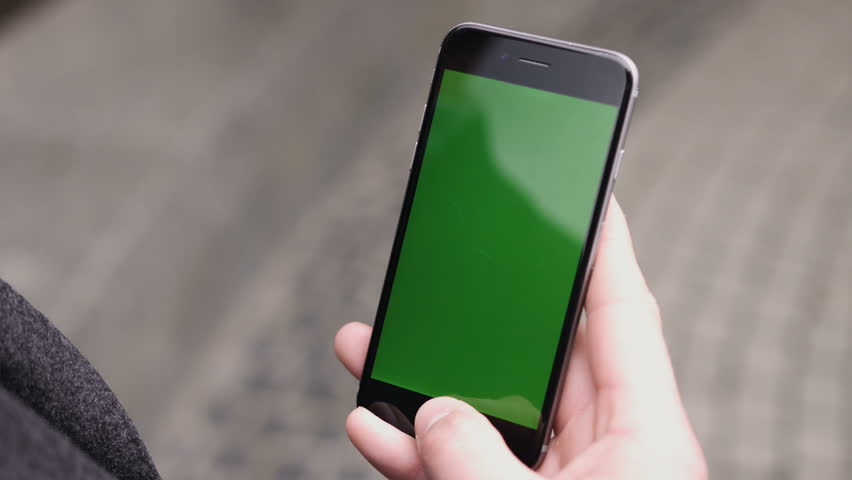 Closeup of a man's hand holding a mobile telephone with a vertical green screen on the streets.