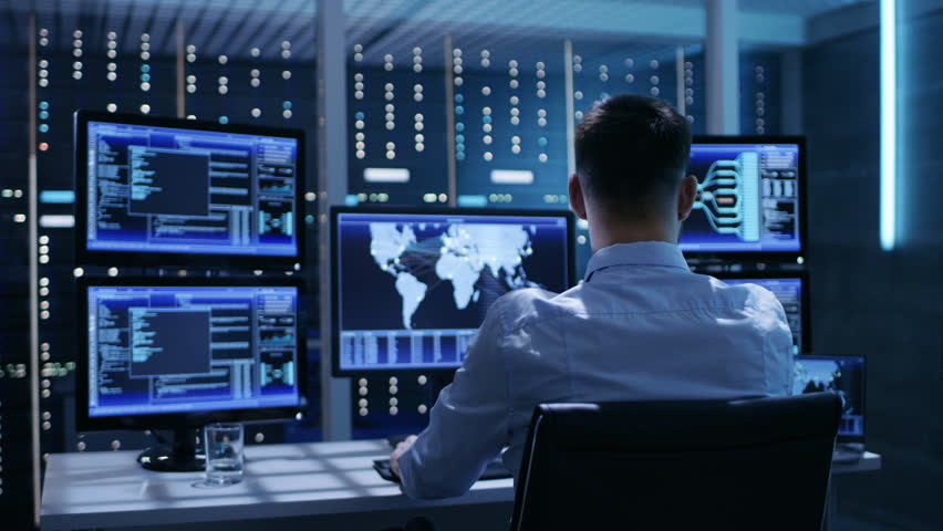 Technical Controller Working at His Workstation with Multiple Displays. Displays Show Various Technical Information. He's Alone in System Control Center.  Shot on RED EPIC-W 8K Helium Cinema Camera.