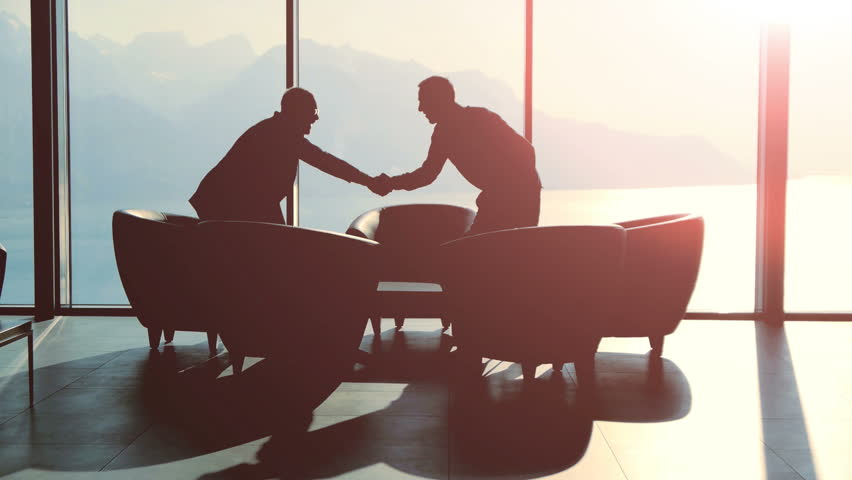 silhouette of two business people talking together sitting in modern lobby hall at sunset light. financial sales corporate concept background  #26264675