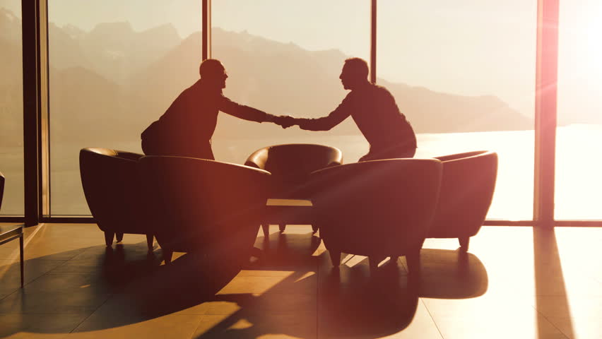 Business partners meeting inside modern lobby hall chatting over contract agreement deal. businessman handshaking scene background | Shutterstock HD Video #26264768