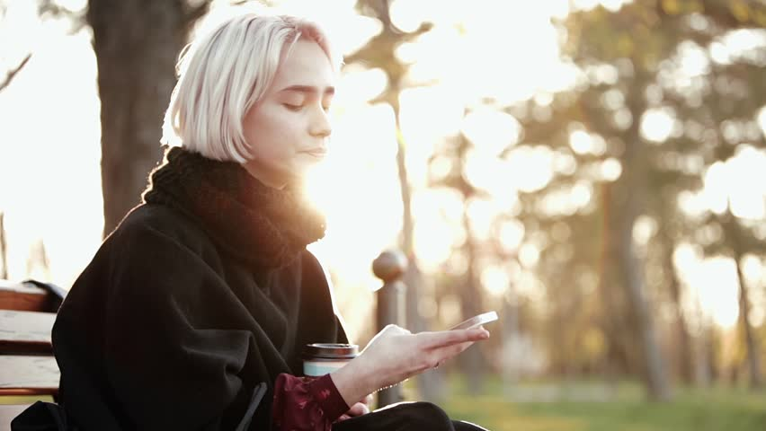 Blonde woman girl outside. In the hands of a smartphone and coffee. Sits on a wooden bench. He looks at the smartphone, turns abruptly at the camera. Surprise on the face. Called