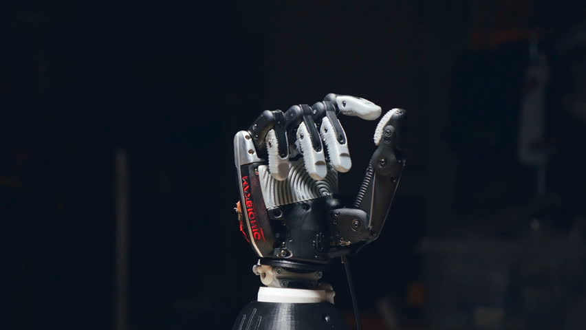 The camera is slowly moving around the robot hand, showing how it is opening the fingers. The thumb is moving to the right. | Shutterstock HD Video #26296868