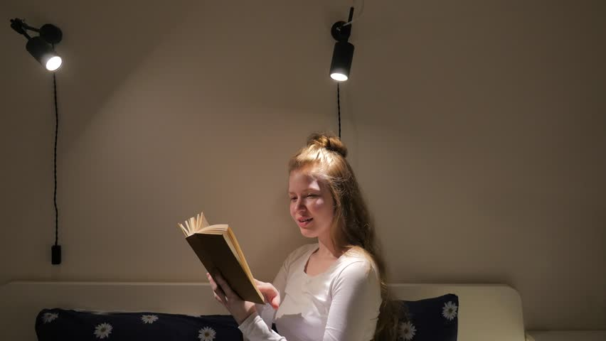 Girl reading book and showing happy emotions. Blonde girl sitting on the bed and holding book. Nighttime reading. Relaxed woman enjoying reading book before sleep.  | Shutterstock HD Video #26311157