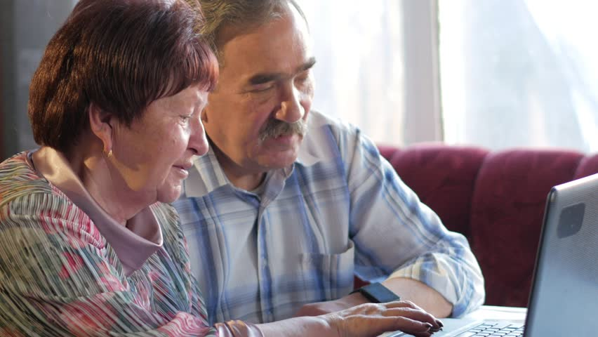 An elderly couple is sitting at home at the laptop. A woman reads news, a man with a mustache sits next to him and talks #26312399